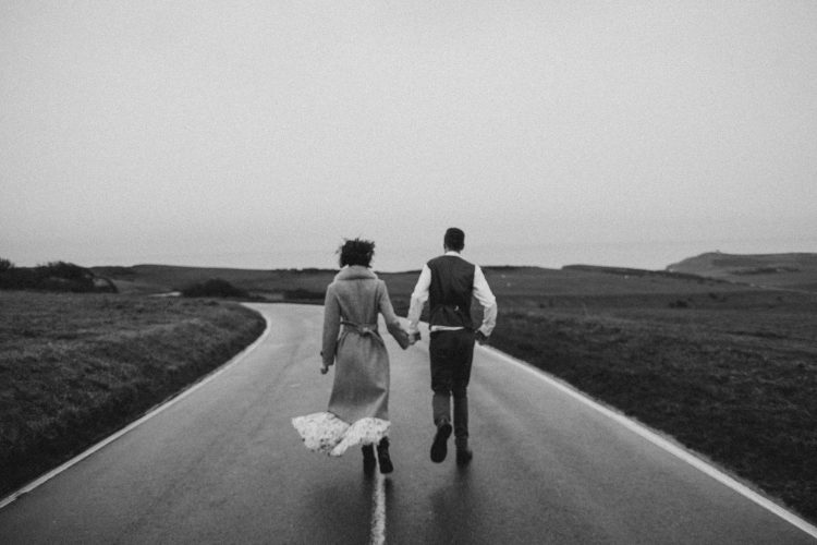 grayscale-photo-of-couple-walking-on-road